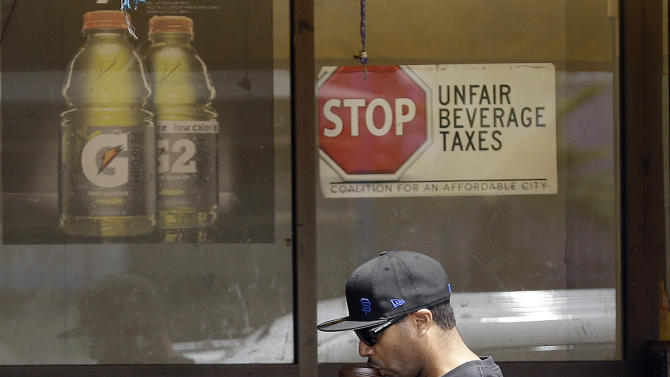 In this July 7, 2014 photo, a man drinks out of a coffee cup as he walks under a sign opposed to taxes on sugary drinks posted in the window of Casa Thai Market in San Francisco. San Francisco and Berkeley are aiming to become the first U.S. cities to pass per-ounce taxes on sugary drinks. (AP Photo/Jeff Chiu)