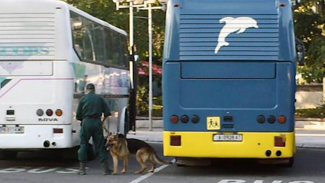 A Bulgarian policeman with a sniffer dog checks busses for explosives buses at , Burgas airport, outside the Black Sea city of Burgas, Bulgaria, some 400 kilometers (250 miles) east of the capital, Sofia, Wednesday, July 18, 2012. A bus carrying young Israeli tourists in a Bulgarian resort exploded Wednesday, killing several people and wounding at least 24, police said. Witnesses told Israeli media that the huge blast occurred soon after someone boarded the vehicle. (AP Photo/ Impact press Group)