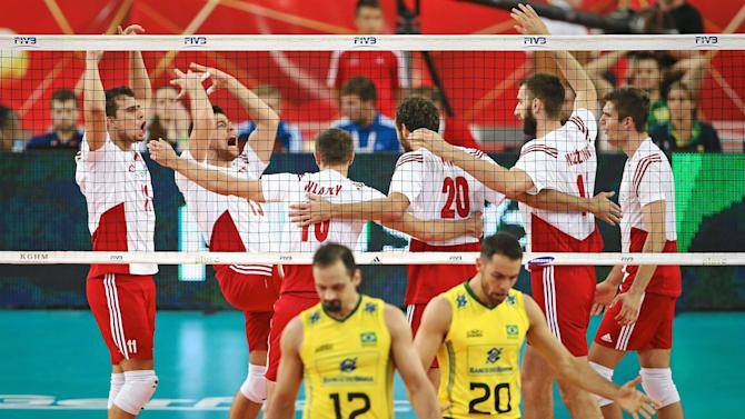 Brazilian players reacts as Polish players celebrate their victory in their third round match of the FIVB Volleyball Men's World Championship Poland 2014 at the Atlas Arena in Lodz