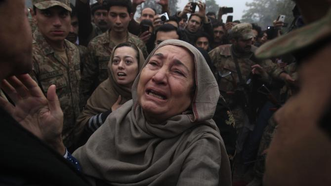 Grandmother and mother of Muhammad Ali Khan, a student who was killed during an attack by Taliban gunmen on Army Public School, react during a visit by Imran Khan, at the school in Peshawar