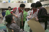 In this photo released by Japanese Red Cross Society, a survivor woman is tended by members of Japanese RC's National Disaster Response Team at the Ishinomaki Red Cross Hospital in Ishinomaki in Miyagi Prefecture (state), Saturday, March 12, 2011, one day after the catastrophic earthquake and tsunami hit northeastern Japan.