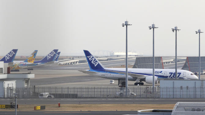 All Nippon Airways planes including a Boeing 787, right, are parked at Haneda Airport in Tokyo Wednesday afternoon, Jan. 16, 2013. ANA said a cockpit message showed battery problems and a burning smell were detected in the cockpit and the cabin, forcing another Boeing 787 on a domestic flight to land at Takamatsu airport in western Japan Wednesday morning. (AP Photo/Shizuo Kambayashi)