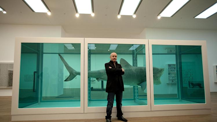"British artist Damien Hirst poses for photographers beside the 1991 piece ""The Physical Impossibility of Death in the Mind of Someone Living"", a tiger shark preserved in formaldehyde in a vitrine, during a media preview of the first substantial survey show of his work in the UK at the Tate Modern gallery in London, Monday, April 2, 2012.  The exhibition, timed for the culmination of the Cultural Olympiad and due to open to the public on Wednesday, showcases over 70 of Hirst's works since he first came to public attention in 1988.  (AP Photo/Matt Dunham)"