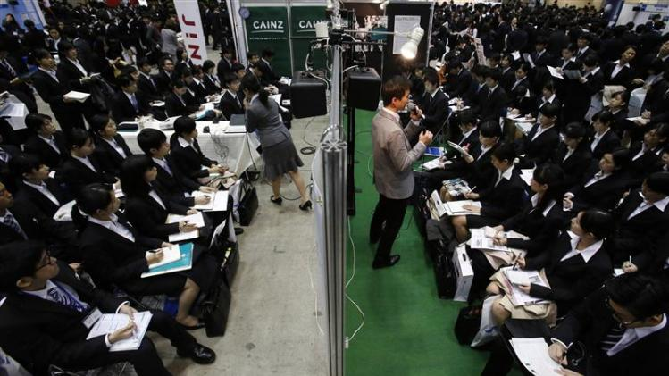 Job seekers listen to presentations during a job fair held for fresh graduates in Tokyo