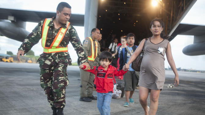 An Airman with the Philippines Air Force helps offload Filipino civilians out of a U.S. Marine Corps C-130 Hercules aircraft at Villamor Air Base, Philippines. U.S. service members are assisting the Armed Forces of the Philippines in the recovery efforts for the people affected in the aftermath of Typhoon Haiyan. (AP Photo/NMCS, Cpl. Codey Underwood)