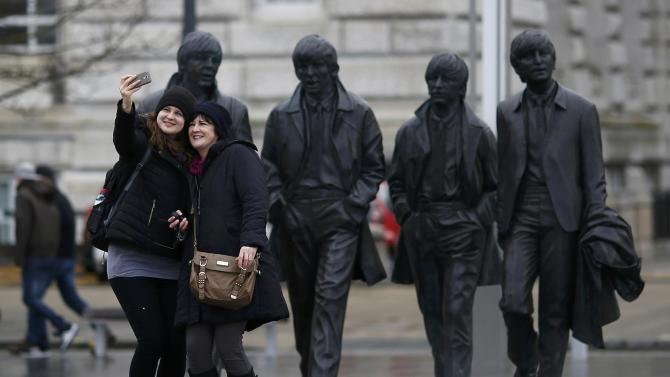 Tourists pose for a selfie in front of a statue of The Beatles  in Liverpool northern England