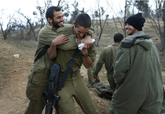 An Israeli soldier, left, hugs a comrade, center, to congratulate him for his birthday at a staging area near the Israel Gaza Strip Border, southern Israel, Thursday, Nov. 22, 2012. A cease-fire agree