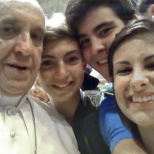 """FILE - In this file photo Wednesday, Aug. 28, 2013 released Friday, Aug. 30, 2013 by Miss Deborah Arcelli and taken on a mobile phone by her son Riccardo, second from left, Pope Francis has his picture taken inside St. Peter's Basilica with youths from the Italian Diocese of Piacenza and Bobbio who came to Rome for a pilgrimage, at the Vatican. """"Selfie"""" the smartphone self-portrait has been declared word of the year for 2013 by Britain's Oxford University Press. (AP Photo/Riccardo Aguiari, File)"""