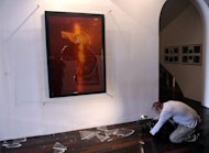 "A cameraman films in Avignon on April 2011, broken piece of glass from ""Immersion Piss Christ"", a controversial piece of art by US artist Andres Serrano, after its partially destruction by two catholic activists"