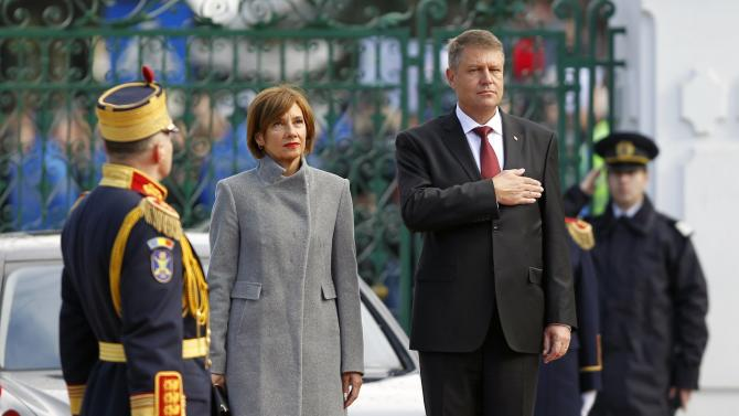 Romania's new President Iohannis and his wife Carmen listen to the national anthem during a take-over ceremony at Cotroceni presidential palace in Bucharest