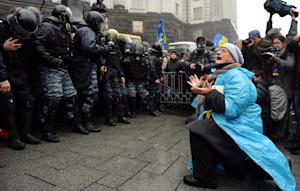 A woman kneels in front of riot police riot police…