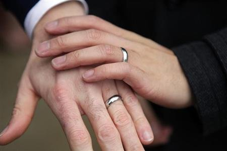 Bernie Liang (L), and Ryan Hamachek, show their rings after getting married outside Seattle City Hall in Seattle, Washington December 9, 2012. REUTERS/Cliff Despeaux