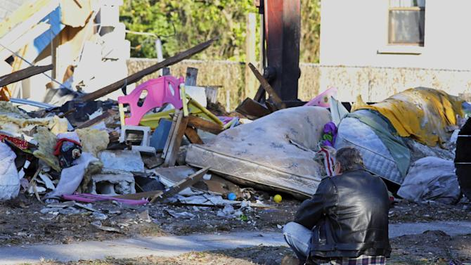 A family member prays in front of home of Jeff Bush, 37, before demolition crews destroy it Monday, March 4, 2013, after a sinkhole opened up underneath it late Thursday evening swallowing Bush, 37, in Seffner, Fla. The 20-foot-wide opening of the sinkhole was almost covered by the house, and rescuers said there were no signs of life since the hole opened Thursday night.  (AP Photo/Scott Iskowitz)