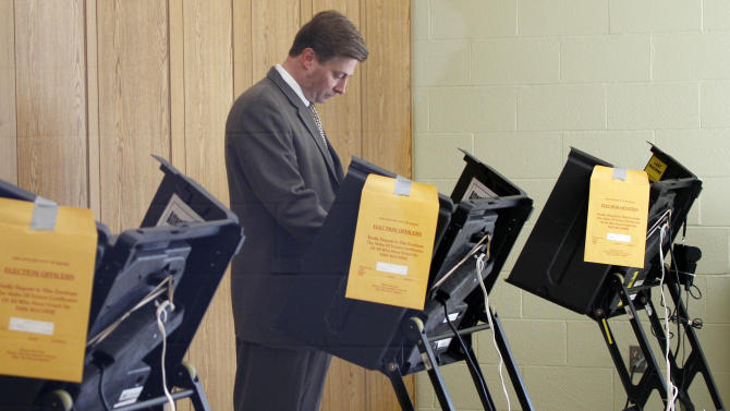 U.S. Rep. Jason Altmire, D- Pa., is seen through a window as he votes in the Pennsylvania primary election on Tuesday, April 24, 2012 in McCandless, Pa., a suburb north of Pittsburgh. Altmire faces fellow U.S. Rep. Mark Critz after the Legislature and governor approved new lines combining their previously separate districts into the new District 12. (AP Photo/Keith Srakocic)