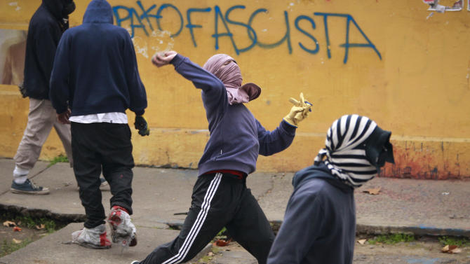 A protester throws stones at police near the entrance of the University of Chile during a national strike in Santiago, Chile, Wednesday Aug. 24, 2011.  A nationwide strike shutting down Chile for two days has begun with people stoning buses and police clearing nearly two-dozen burning barricades around the capital of Santiago.  (AP Photo/Victor R. Caivano)