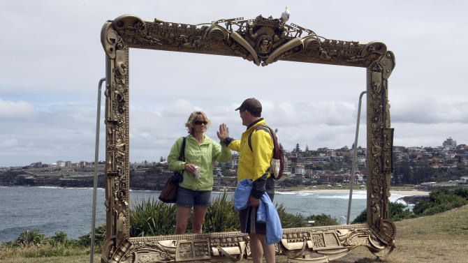 In this Nov. 3, 2011 file photo, a couple pretend to be a mirror image of each other in Jane Gilling's sculpture, Provenance (a gift frame) at Sculptures By The Sea in Sydney, Australia. Every November, the popular Sculpture by the Sea exhibition features large art installations placed along the path and beaches, providing a free seaside art show. (AP Photo/Rob Griffith)