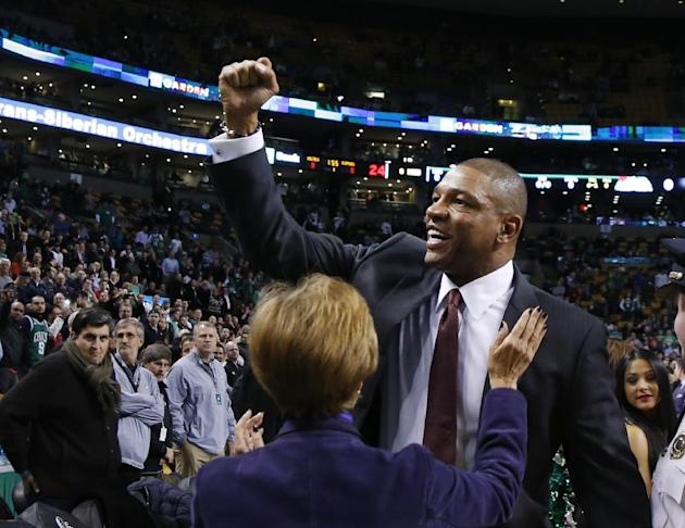 Doc Rivers, former head coach of the Boston Celtics and current head coach of the Los Angeles Clippers, acknowledges cheering fans as he enters the TD Garden floor for his first time back, before an N