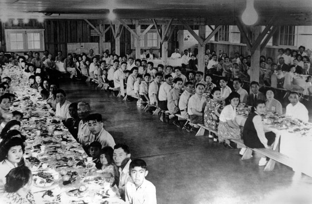"In this 1942 photo provided by the War Relocation Authority, Japanese American detainees are seen in a mess hall at the Fresno Assembly Center in Fresno, Calif. Before being shipped to permanent internment camps, most Japanese were rounded up and detained for months in temporary ""assembly centers"" such as this one, in often primitive conditions and under the watch of armed guards. (AP photo/War Relocation Authority)"