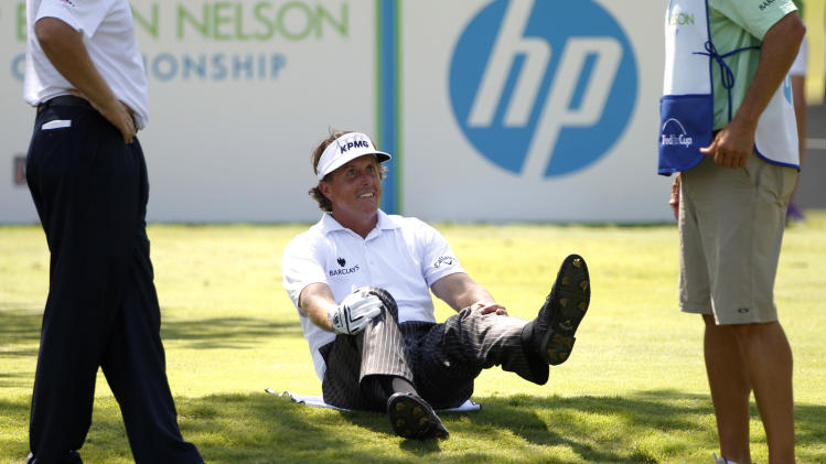 "Phil Mickelson, center, stretches on the ground as he talks with Ernie Els, left, and his caddie, Jim ""Bones"" McKay, right, as the trio wait for the fairway to clear from the seventh tee box during the first round of the Byron Nelson Championship golf tournament Thursday, May 17, 2012, in Irving, Texas. (AP Photo/Tony Gutierrez)"