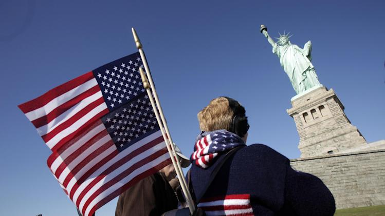 Donna Bodkins, of Fisher, West Virginia, caries American flags while visiting the Statue of Liberty to mark her 125th anniversary, Friday, Oct. 28, 2011 in New York. (AP Photo/Mark Lennihan)