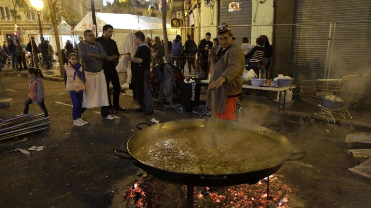 "A man cooks a huge paella on the street during the ""Fallas"" festival in Valencia"