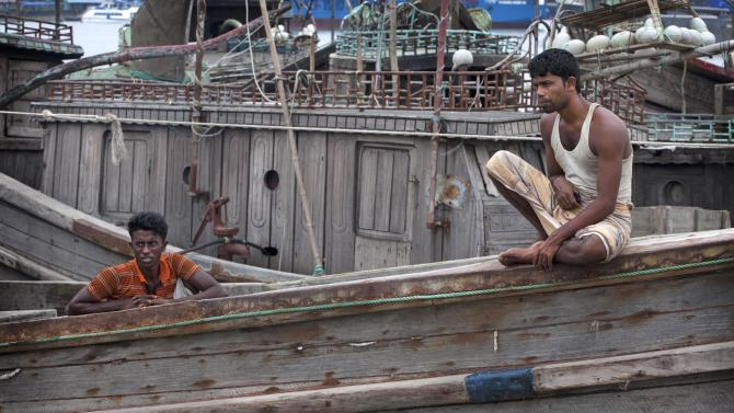 Bangladeshi fishermen sit on their boat on the banks of the river Kornofuli, in Chittagong, Bangladesh, Wednesday, May 15, 2013. Cyclone Mahasen is expected to make landfall early Friday. The storm was heading toward Chittagong, Bangladesh, but could shift east and deliver a more direct hit on Rakhine state in Myanmar. (AP Photo/ A.M.Ahad)