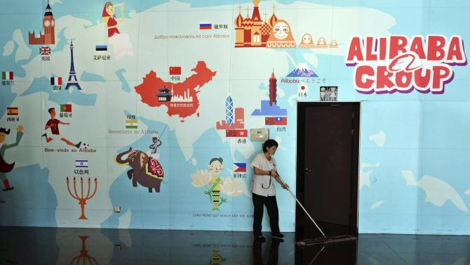 Cleaner sweeps the floor in front of a picture on the wall of a world map, at the headquarters of Alibaba Group on the outskirts of Hangzhou