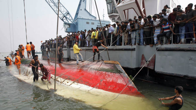 Recovery workers attempt to lift the wreckage of a ferry that capsized in the Meghna River in Munshiganj district, about 20 miles (32 kilometers) south of Dhaka, Bangladesh, Wednesday, March 14, 2012. The ferry, carrying about 200 people, collided with a cargo boat and capsized in the darkness of Tuesday morning, sending hundreds of people into the Meghna River, just south of the capital, Dhaka. The death toll rose to 110 while dozens of passengers still remain missing.  (AP Photo/Pavel Rahman)