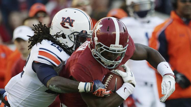 Alabama running back T.J. Yeldon (4) is stopped by Auburn linebacker Daren Bates (25) during the first half of a NCAA college football game at Bryant-Denny Stadium in Tuscaloosa, Ala., Saturday, Nov. 24, 2012. (AP Photo/Dave Martin)