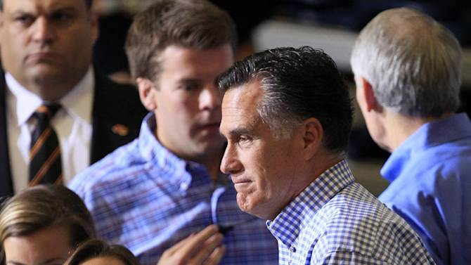 Republican presidential candidate, former Massachusetts Gov. Mitt Romney hands a pack of bottled water to a student as he helped collect donations at a storm relief event, Tuesday, Oct. 30, 2012, at James S. Trent Arena in Kettering, Ohio. (AP Photo/Al Behrman)