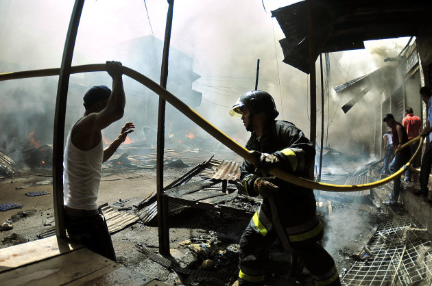 A firefighter is helped by residents with a hose during a blaze at a street market in Tegucigalpa, Honduras, Saturday Feb. 18, 2012. The fire burned through several blocks of wooden stalls and there are no immediate reports of deaths or serious injuries from the fire, according to Mayor Ricardo Alvarez. (AP Photo/Fernando Antonio)