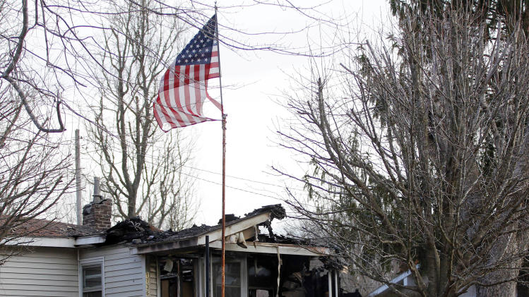 A U.S. flag flies near the charred remains of a home Sunday, March 10, 2013, in Gray, Ky., where a fire erupted Saturday, killing two adults and five children inside. (AP Photo/Lisa Norman-Hudson)