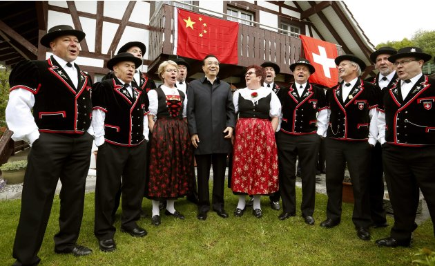 Chinese Premier Li Keqiang stands between the members of the Jodelclub Saengerrunde Zurich yodel band during his visit to Guldenberg farm in Embrach