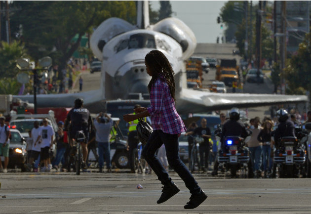 A young woman runs across the street in front of the space shuttle Endeavour as it is slowly moved down Crenshaw Blvd., Saturday, Oct.13, 2012, in Los Angeles. The shuttle is on its last mission — a 1