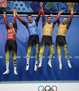 The German team of Natalie Geisenberger, in orange, Felix Loch, in blue, and doubles team of Tobias Wendl and Tobias Arlt, in yellow, leap onto the podium after winning the gold medal during the luge team relay competition at the 2014 Winter Olympics, Thursday, Feb. 13, 2014, in Krasnaya Polyana, Russia. (AP Photo/Michael Sohn)