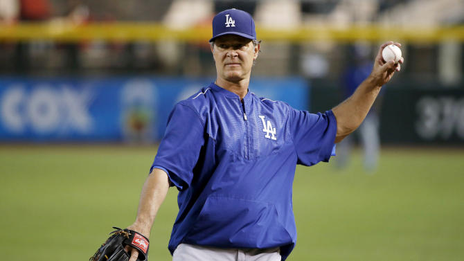 Los Angeles Dodgers manager Don Mattingly warms up with his players prior to a baseball game against the Arizona Diamondbacks on Wednesday, July 1, 2015, in Phoenix. (AP Photo/Ross D. Franklin)