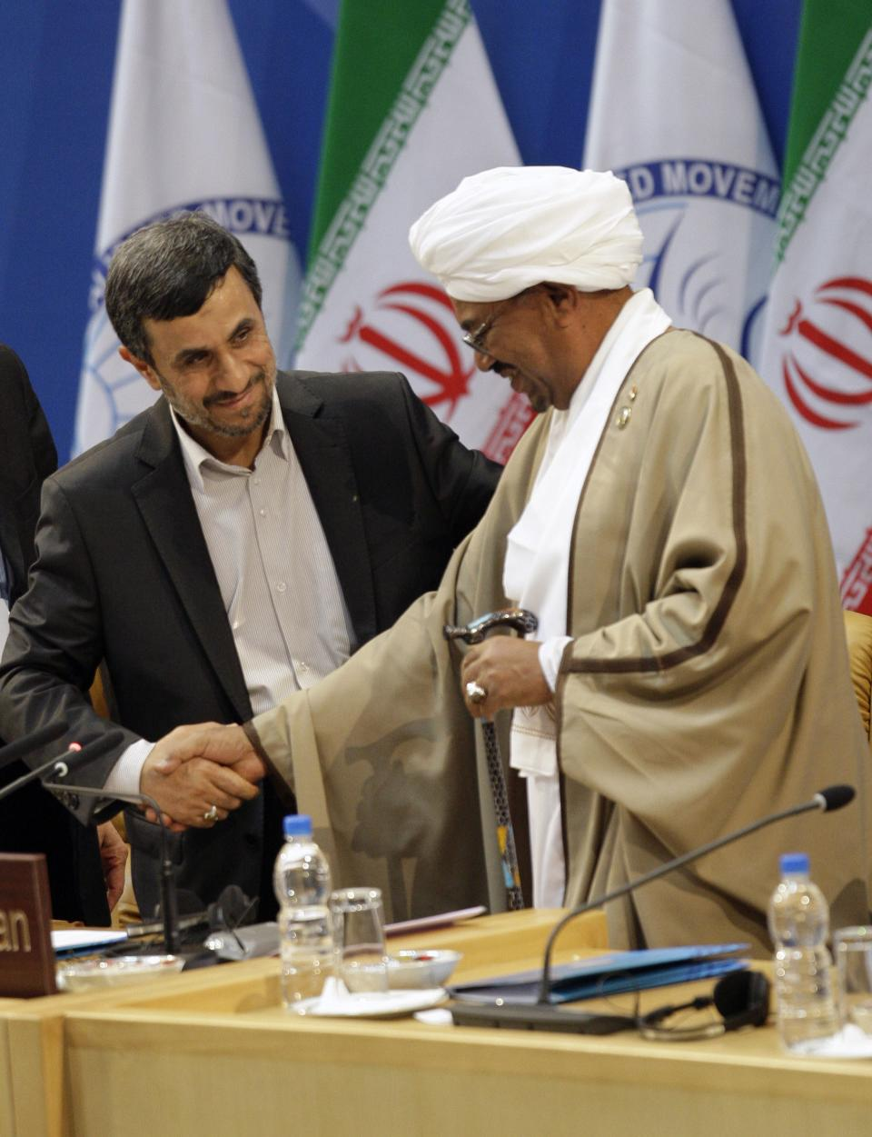 Iranian President Mahmoud Ahmadinejad, left, welcomes Sudanese President Omar al-Bashir, right, at the Nonaligned Movement summit in Tehran, Iran, Friday, Aug. 31, 2012. (AP Photo/Vahid Salemi)