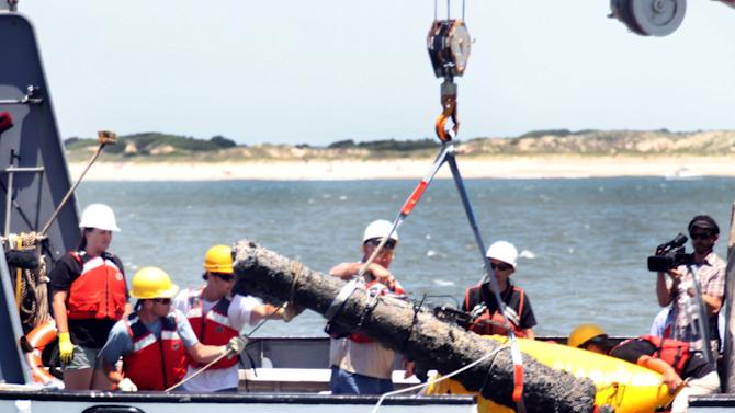 In this Thursday, June 20, 2013 photo, divers emerge with the second of two cannons raised from the wreck of the Queen Anne's Revenge off the coast of Carteret County, N.C. Blackbeard captured a French slave ship and renamed it Queen Anne's Revenge in 1717. Volunteers with the Royal Navy killed Blackbeard in Ocracoke Inlet the following year, five months after the ship sank. There's a $450,000 effort under way to remove all the artifacts from the ship by the end of next year. (AP Photo/The Jacksonville Daily News, Chuck Beckley)