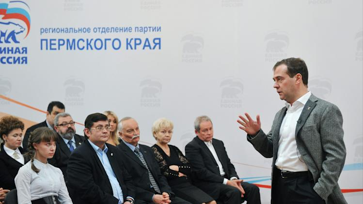 "Russian Prime Minister Dmitry Medvedev, right, meets with activists of the United Russia party in the city of Perm, about 1200 kilometers (750 miles) east of Moscow, Tuesday, Oct. 30, 2012. The sign reads, ""Perm regional branch of the United Russia party"". (AP Photo/RIA-Novosti, Alexander Astafyev,  Government Press Service)"