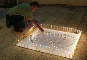 """A man places a candle on a white board spelling out """"MH370"""" during a candlelight vigil for the the missing Malaysia Airlines flight, in Kuala Lumpur"""