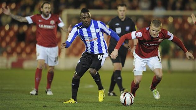Barnsley's Tomasz Cywka is challenged by Sheffield Wednesday's Jermaine Johnson (left)