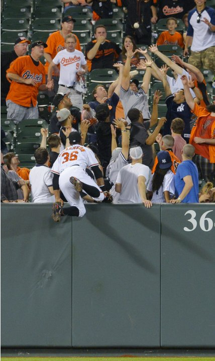 Baltimore Orioles' Dickerson leaps into the stands on a hit by New York Yankees' Hafner during their MLB game in Baltimore