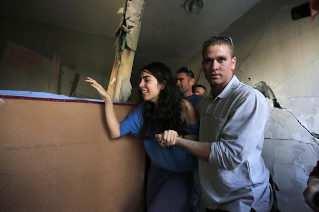 Israelis Sapir, left, and her boyfriend Ron, right, last names not given, walk inside Sapir's home, hit by a rocket fired by militants from Gaza Strip, in the southern city of Beersheba, Israel, Tuesd