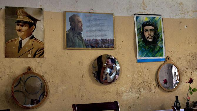 "A man smoking a cigarette is reflected in a mirror hanging on his home's wall covered with photographs of Cuba's President Raul Castro, top left, Fidel Castro, top center, and late revolutionary hero Ernesto ""Che"" Guevara, top right, in Old Havana, Cuba, Saturday, Oct. 20, 2012. On Sunday, Cubans will cast ballots to choose among candidates for municipal assemblies that administer local governments and relay complaints on issues such as potholes and housing, social and sports programs. (AP Photo/Ramon Espinosa)"