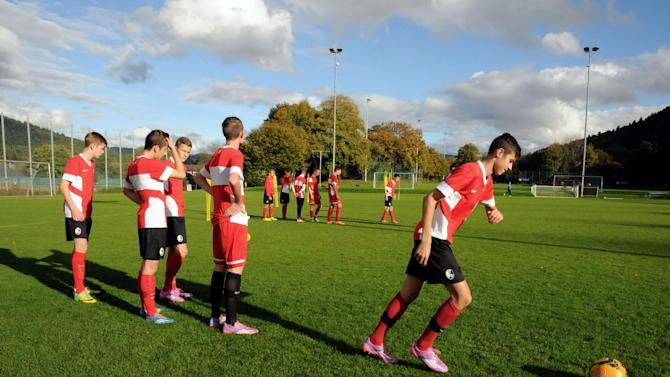 """In this photo taken Saturday, Oct. 18, 2014, players go through their paces at Freiburg's football academy in Freiburg, Germany. As one of the Bundesliga's most financially disadvantaged teams, Freiburg deploys an array of coping strategies to stay in Germany's top division and remain competitive against rival clubs that have richer resources, revenues and budgets. Because Freiburg cannot afford to buy many players, it """"builds"""" them instead, plowing about 6 million euros (US$7.5 million) per year - roughly 10 percent of its annual revenues - into its academy. (AP Photo/John Leicester)"""