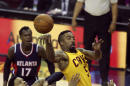 Cleveland Cavaliers' J.R. Smith (5) passes over Atlanta Hawks' Kent Bazemore and Al Horford (15) during the first half in Game 3 of the Eastern Conference finals of the NBA basketball playoffs Sunday, May 24, 2015, in Cleveland. (AP Photo/Ron Schwane)