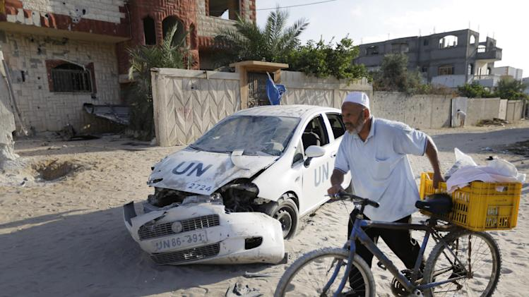 A Palestinian walks with his bicycle past a United Nations aid agency car that was damaged by shrapnel from an Israeli strike, in the Jebaliya refugee camp, in the northern Gaza Strip, Tuesday, July 29, 2014. On Tuesday evening residents of the sprawling camp reported intense tank shelling. U.N aid agency worker Mounir Haggar and his brother Bassir who were in the car were killed and Mounir's son Ibrahim, 12, was wounded. (AP Photo/Lefteris Pitarakis)