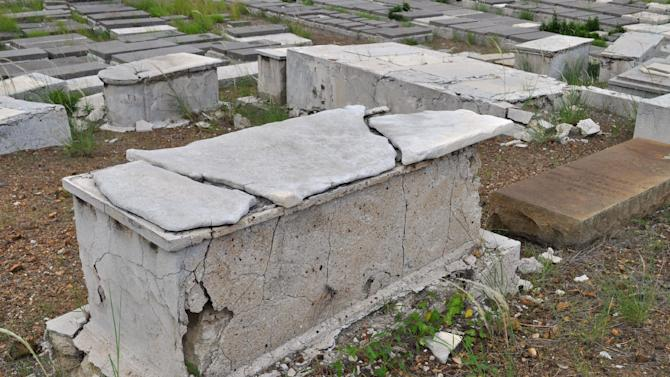 In this Nov. 12, 2012 photo, a crumbling tomb stands in the Beth Haim cemetery in Blenheim on the outskirts of Willemstad, Curacao. Beth Haim, believed to be one of the oldest Jewish cemeteries in the Western Hemisphere, established in the 1950s and considered an important landmark on an island where the historic downtown has been designated a UNESCO World Heritage Site, is slowly fading in the Caribbean sun. Headstones are pockmarked with their inscriptions faded, stone slabs that have covered tombs in some cases for hundreds of years are crumbling into the soil, marble that was once white is now grey, likely from the acrid smoke that spews from the oil refinery that looms nearby. (AP Photo/Karen Attiah)