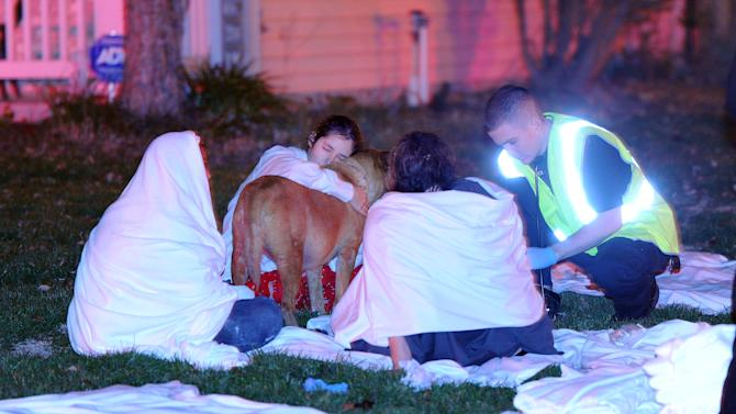 Paramedics attend to the some of the people hurt from the multiple home explosions on the southside of Indianapolis Saturday Nov. 10, 2012. Authorities say a loud explosion has leveled a home in Indianapolis and set four others ablaze in a neighborhood, causing several injuries. Capt. Rita Burris with the Indiana Fire Department told The Associated Press that firefighters are still working to put out the flames after the explosion around 11 p.m. Saturday. (AP Photo/The Indianapolis Star, Matt Kryger)
