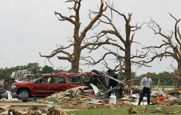 Crushed autos sit amid the rubble as emergency personnel continue search efforts to locate people in that are unaccounted for in the destroyed Rancho Brazos neighborhood of Granbury, Texas, Thursday,